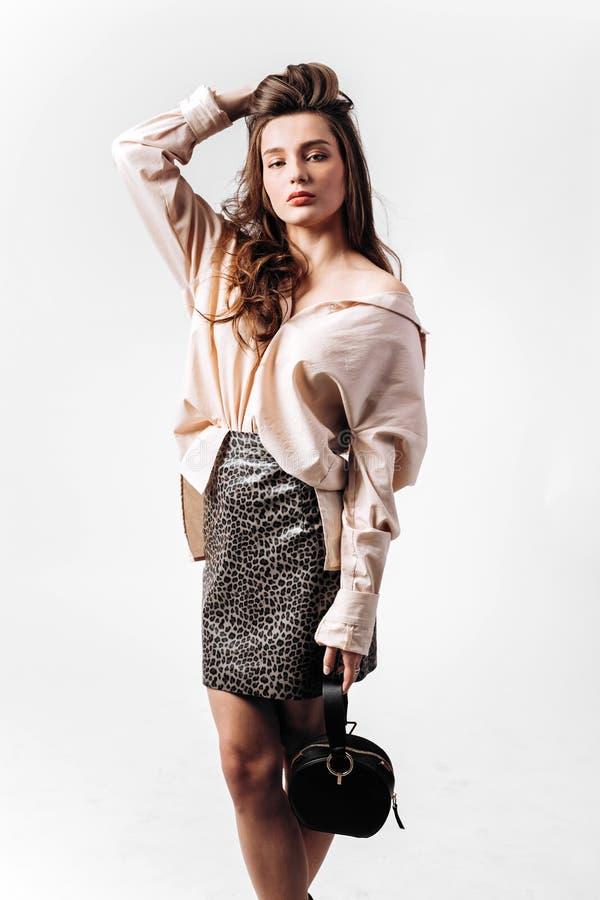 Den iklädda ursnygga flickan en skjorta- och leopardkjol med den lilla svarta påsen poserar på den vita bakgrunden i studion fotografering för bildbyråer