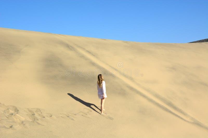 den iklädda viten för kvinna som går runt om öknen royaltyfri bild