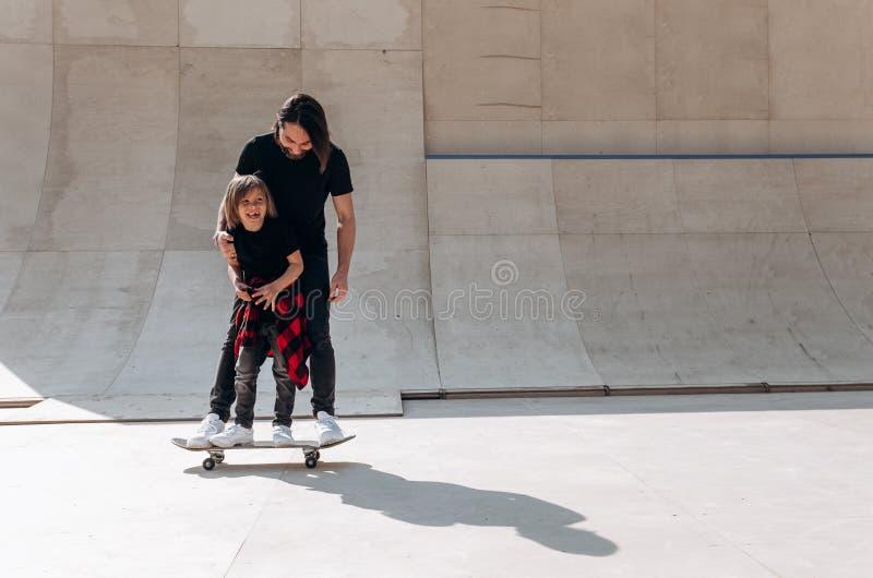Den ikl?dda fadern och hans lilla son den tillf?lliga kl?derna st?r p? den en skateboarden i en skridsko parkerar tillsammans p? royaltyfria bilder