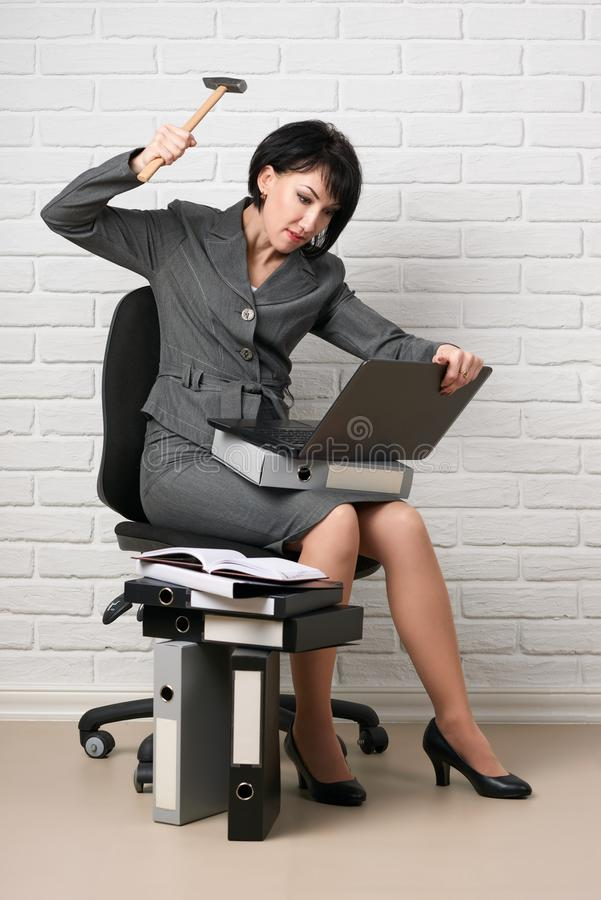 Den ilskna affärskvinnan med bärbara datorn och mappar som har spänningen som är iklädd en grå dräkt, poserar framme av en vit vä royaltyfria bilder