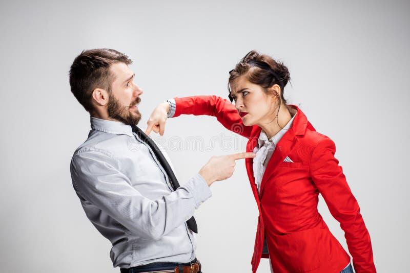 Den ilskna affärsmannen och kvinnan som kämpar på en grå bakgrund royaltyfria bilder