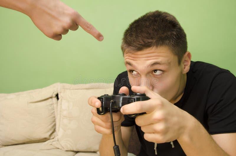 Den ilskna föräldern förbjuder hans unge för att spela videospelet royaltyfria bilder