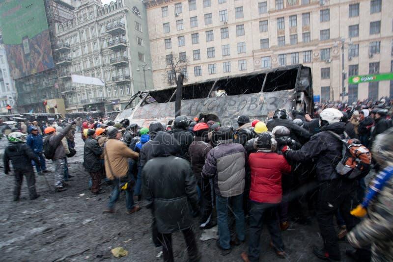 Den ilskna folkmassan på den upptagande gatan valt brännskadan ut bussar på demostrationen under anti--regeringen protesten Euroma royaltyfri fotografi
