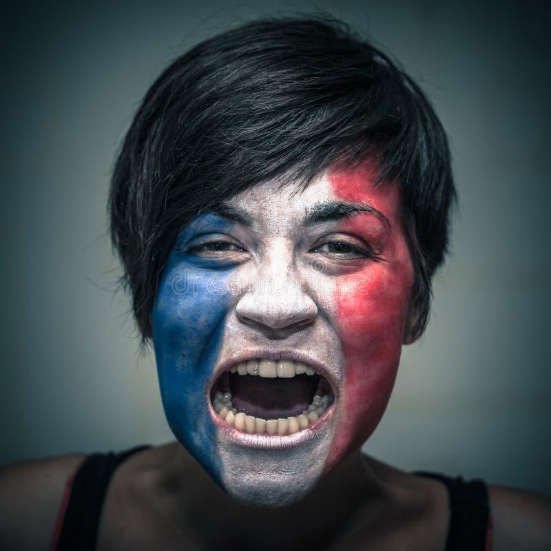Den ilskna kvinnan med flaggan av Frankrike målade på framsida arkivbild