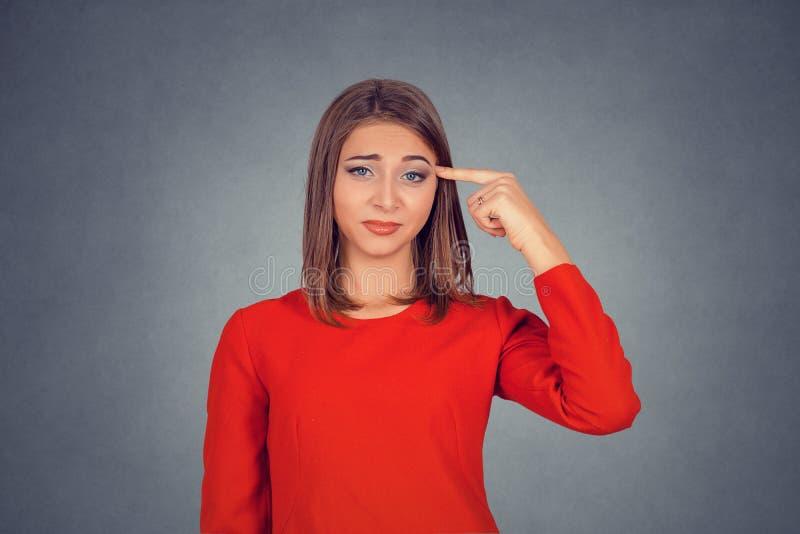 Den ilskna kvinnan som gör en gest med fingret mot templet, är dig som är galen royaltyfria foton