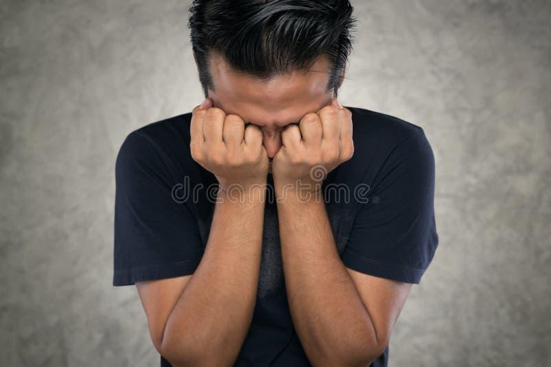 Den ilskna mannen, asiatiska män med deras händer stängde ögon på grund av ilska arkivfoton