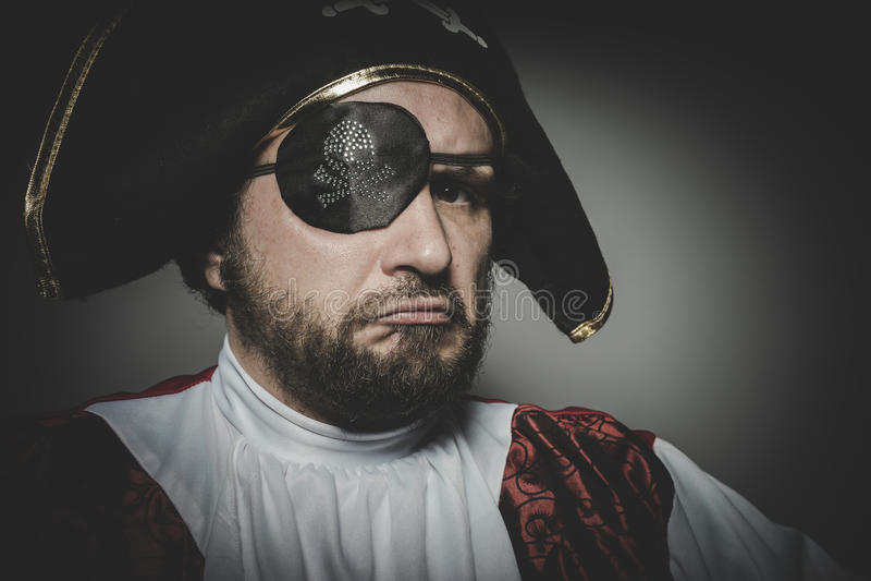 Den ilskna mannen piratkopierar med ögonlappen och den gamla hatten med roliga framsidor och fotografering för bildbyråer