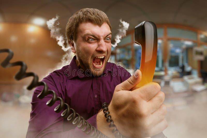 Den ilskna mannen talar på telefonen royaltyfri foto