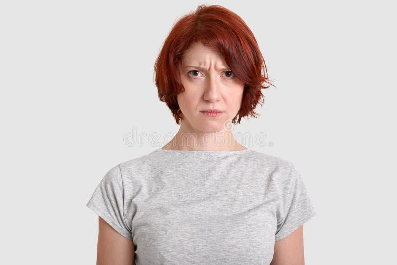 Den ilskna missnöjda kvinnan med rött hår, uttrycker negativa känslor, rynkar pannan framsidan i missnöje, bär den tillfälliga t- royaltyfria foton