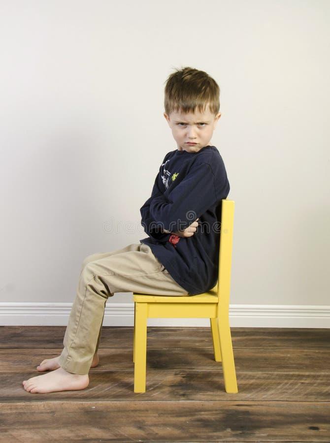 Den ilskna pojken på en gul tid ut presiderar royaltyfria bilder