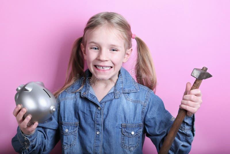 Den ilskna roliga unga flickan med försilvrar spargrisen och hammaren på rosa bakgrund begreppspengar sparar arkivfoto