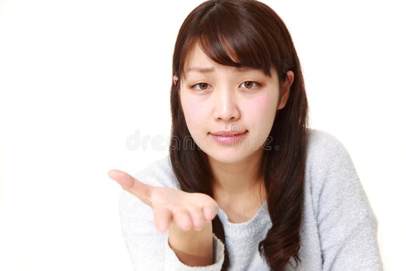 Den ilskna unga japanska kvinnan ber något fotografering för bildbyråer