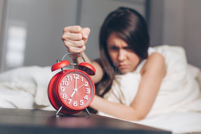 Den ilskna unga kvinnan stansar ringklockan på sängen i morgonen royaltyfria foton