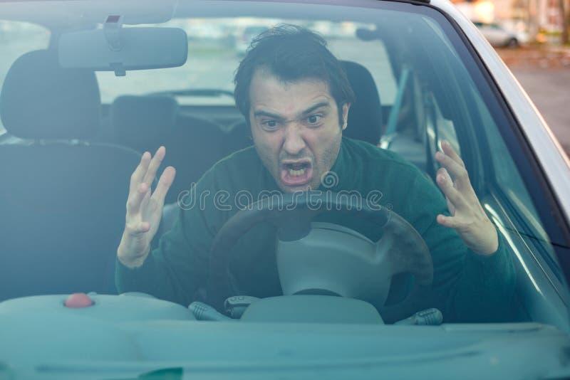 Den ilskna unga mannen som kör ett medel, uttrycker hans vägursinne arkivfoton