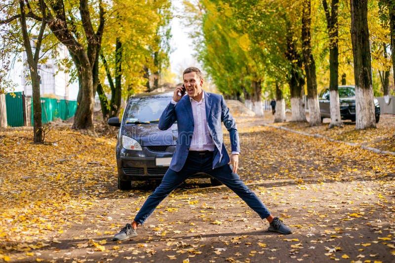 Den ilskna upprivna affärsmannen i dräkt svär känslomässigt på telefonen nära bilen royaltyfria foton