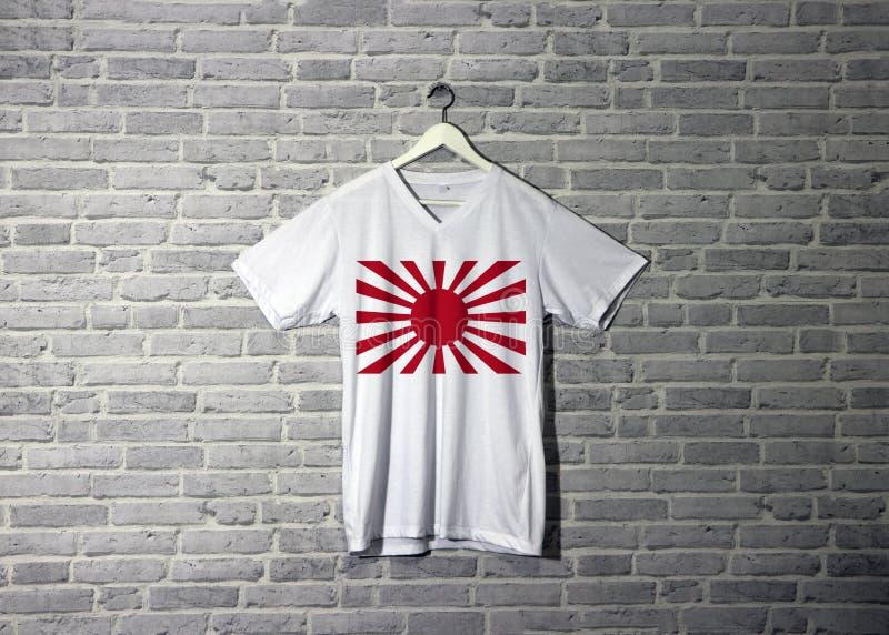 Den imperialistiska krigflaggan för japansk armé på skjortan och hänga på väggen med tegelstenmodelltapeten royaltyfri fotografi