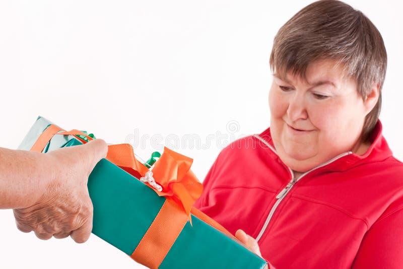 Den inaktiverade kvinnan mottar gåvan från pensionär fotografering för bildbyråer