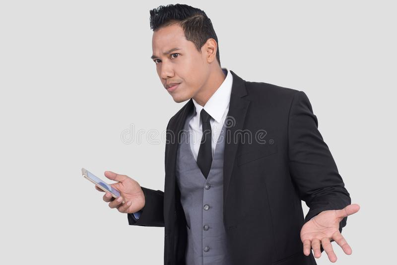 Den indignerade asiatiska affärsmannen som har problem med smartphonen, den korkade dumma grabben som har problem med hans nytt,  royaltyfria foton