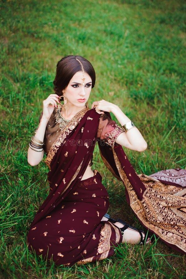 Den indiska flickan med orientaliska smycken och sminkhenna applicerade till handen Hinduisk modellflicka för brunett med indiska fotografering för bildbyråer