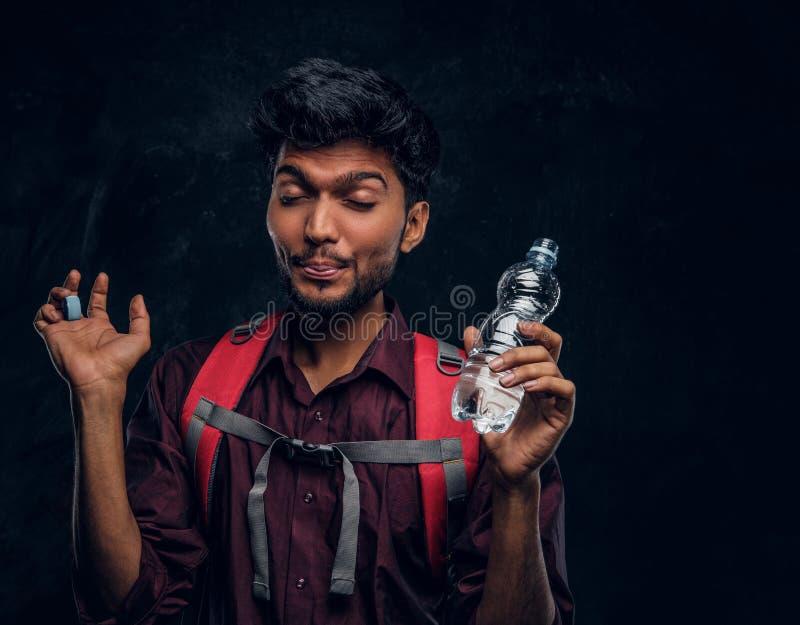 Den indiska fotvandraren med ryggsäcken fick en rörd förnimmelse drack en smutt av sötvatten Texturerat studiofoto mot ett mörkt arkivfoto