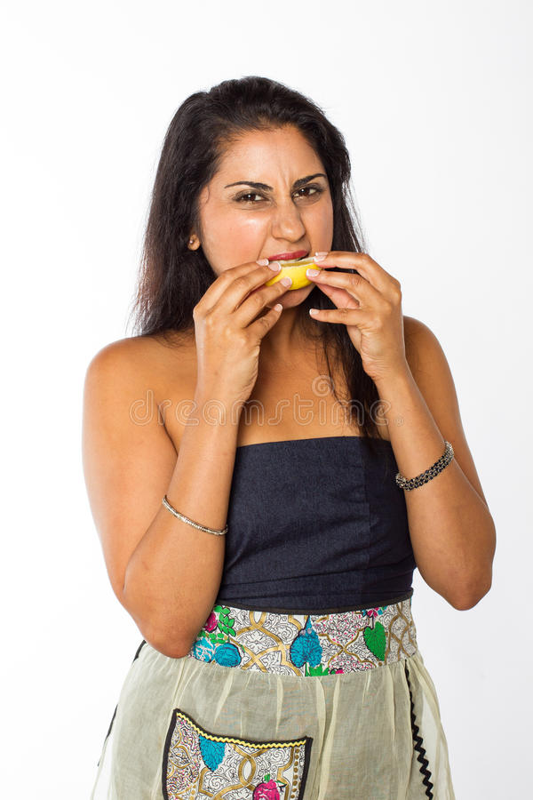 Den indiska kvinnan äter citronen fotografering för bildbyråer