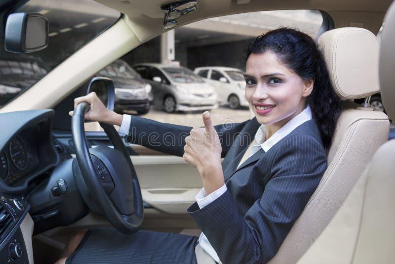 Den indiska kvinnan visar tummen upp i ny bil arkivbild