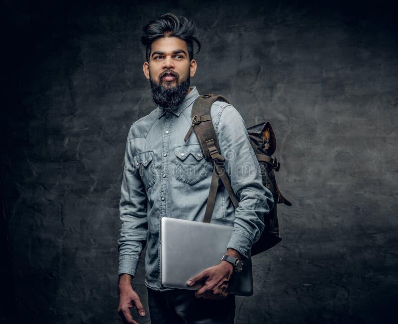 Den indiska manliga studenten rymmer bärbara datorn och ryggsäcken arkivfoton