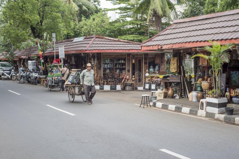 Den indonesiska mannen bär tappningprodukter på den Jalan Surabaya antikviteten och loppmarknaden i Jakarta, Indonesien royaltyfria bilder