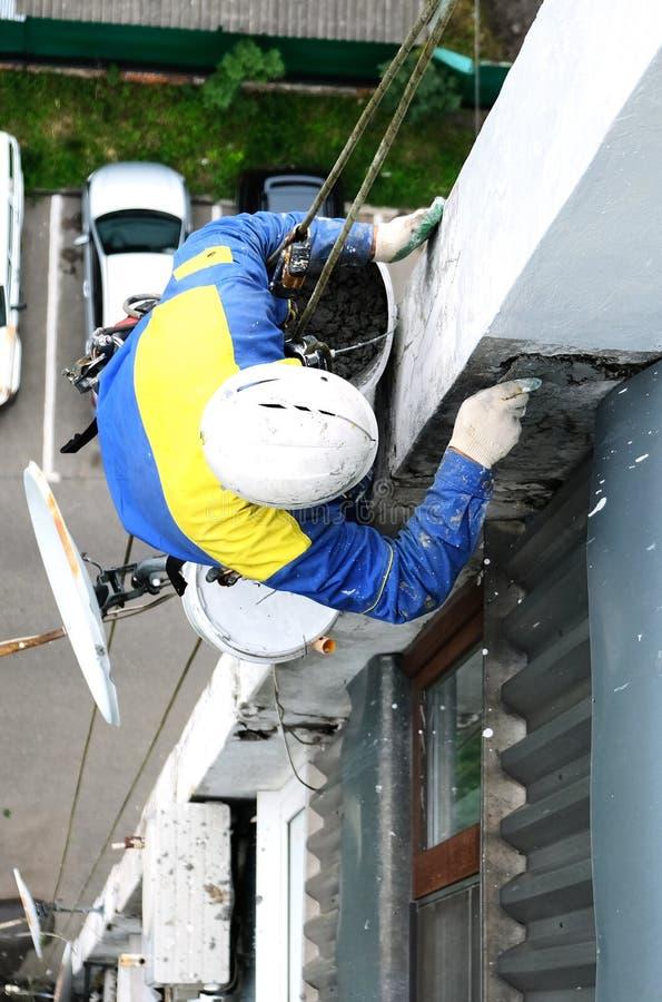 Den industriella klättraren reparerar fasaden av ett hus på en höjd med klättringutrustning arkivbilder