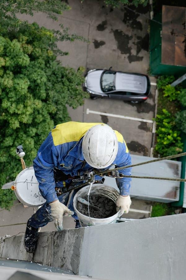 Den industriella klättraren reparerar fasaden av ett hus på en höjd med klättringutrustning royaltyfria bilder