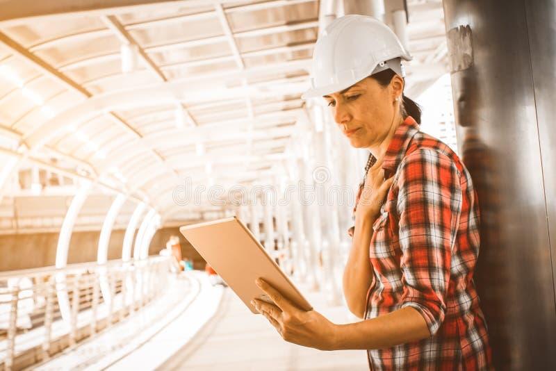 Den industriella konstruktionsteknikern bär teknik för säkerhetshjälmen som arbetar och använder den digitala minnestavlan på byg royaltyfri foto