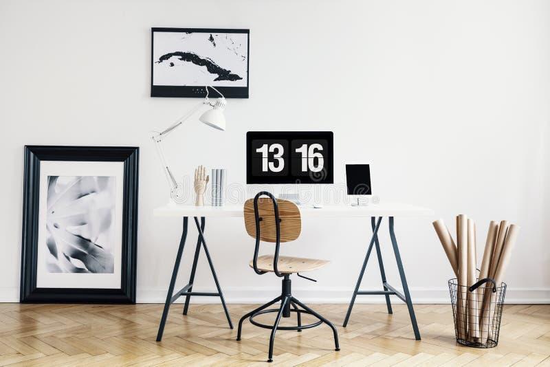 Den industriella korgen med kraft papper rullar och en inramad affisch i en vit, minimalist inrikesdepartementetinre av en freela royaltyfri fotografi