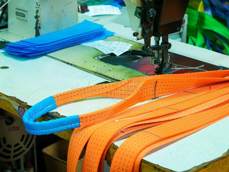Den industriella symaskinen syr en spärrhjulrem royaltyfria foton