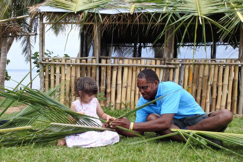 Den infödda Fijianmannen undervisar den unga turist- flickan hur man skapar ett b royaltyfri foto