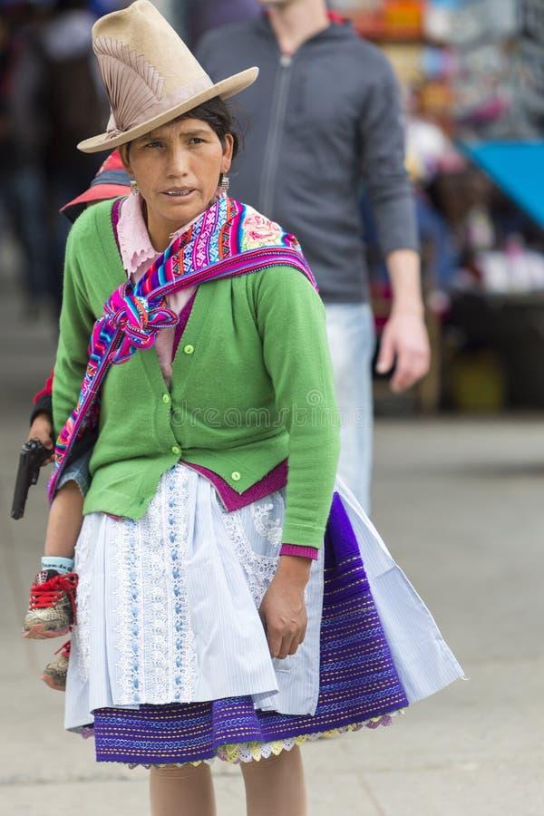 Den infödda indiska kvinnan med henne behandla som ett barn, Peru royaltyfri foto