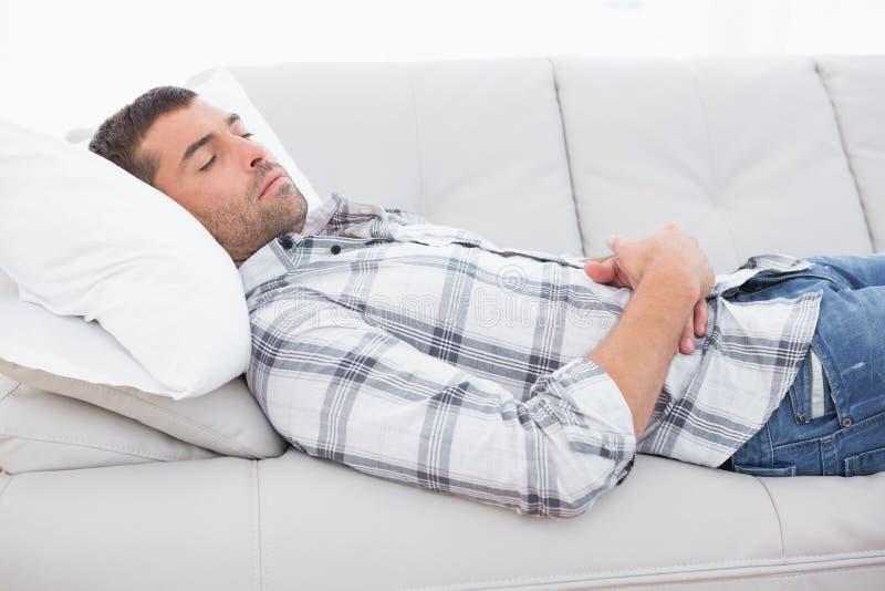 den inhemska liggande mannen kopplar av sofaen royaltyfria bilder