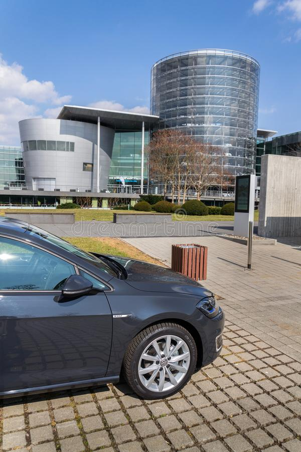 Den inkopplingshybrid- Volkswagen e-golf elbilen står framme av Glasernen Manufaktur - den genomskinliga fabriken, Dresden arkivbilder