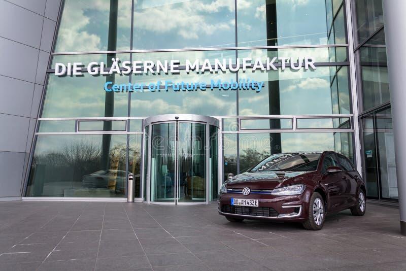 Den inkopplingshybrid- Volkswagen e-golf elbilen står framme av Glasernen Manufaktur - den genomskinliga fabriken, Dresden royaltyfri bild