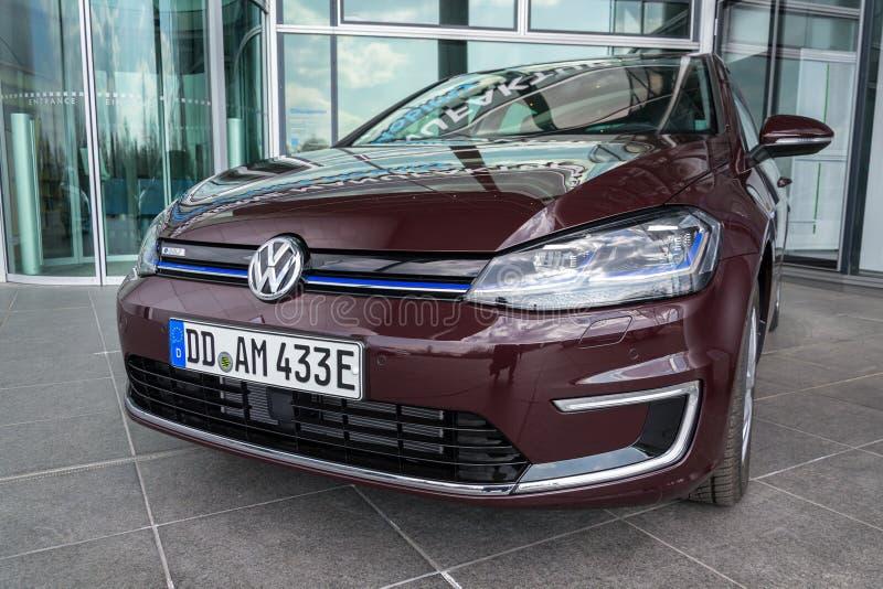 Den inkopplingshybrid- Volkswagen e-golf elbilen står framme av Glasernen Manufaktur - den genomskinliga fabriken, Dresden arkivfoton