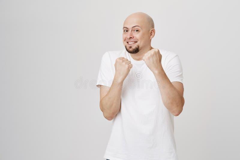 Den inomhus ståenden av det charmiga skämtsamma skalliga caucasian skäggiga mananseendet i boxare poserar försvar som fejkar kamp royaltyfria bilder