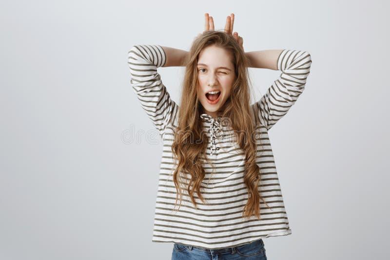 Den inomhus ståenden av den snygga unga europeiska kvinnan som blinkar som rymmer fingrar bak huvudet som, om efterapa öron som k royaltyfria foton