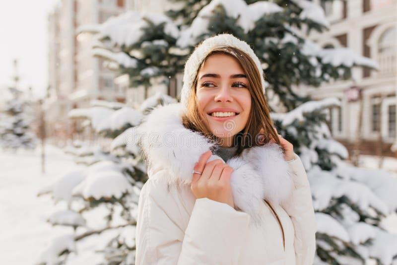 Den inspirerade europeiska damen bär vit vinterdress som tycker om natursikter Utomhus- stående av att bedöva den caucasian kvinn royaltyfria bilder
