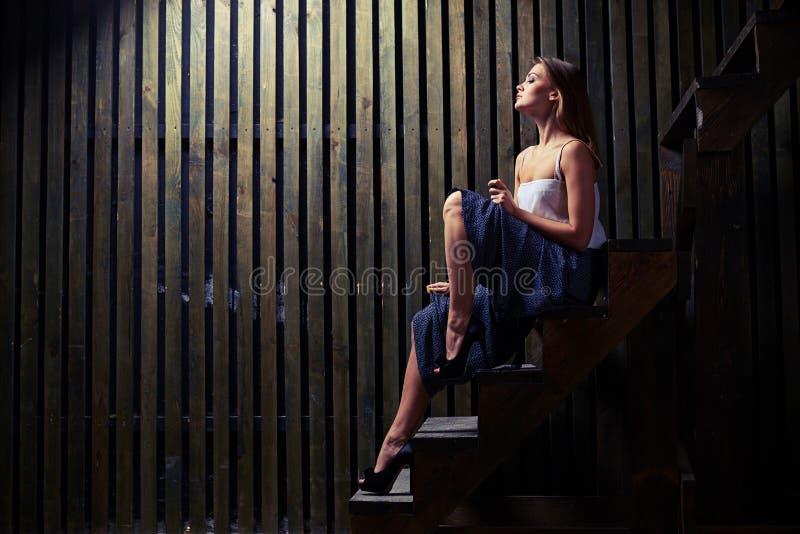 Den inspirerade kvinnan med naket lutar ben som poserar på trätrappa i D royaltyfri fotografi