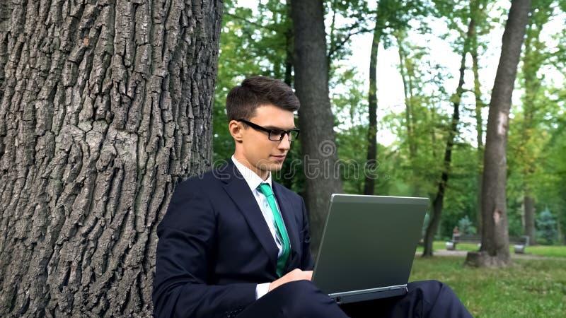 Den inspirerade unga affärsmannen som arbetar på gräs parkerar in och att fly kontorsrutin arkivbild