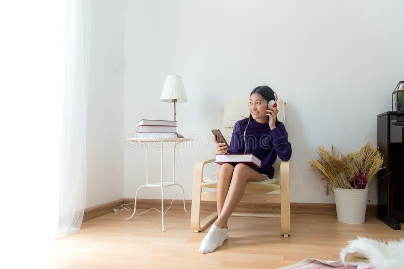 Den inspirerade unga asiatiska kvinnan som hemma lyssnar musiken, kopplar av och lyckligt liv arkivfoto