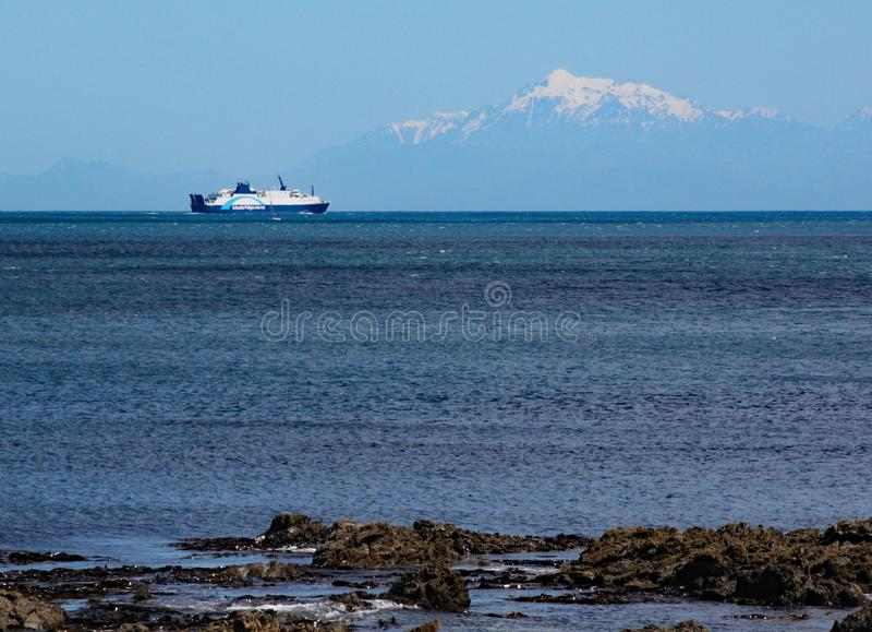 Den Interislander färjan på kocken Strait seglar in mot den södra ön De korkade bergen för snö kan ses i bakgrunden royaltyfria bilder