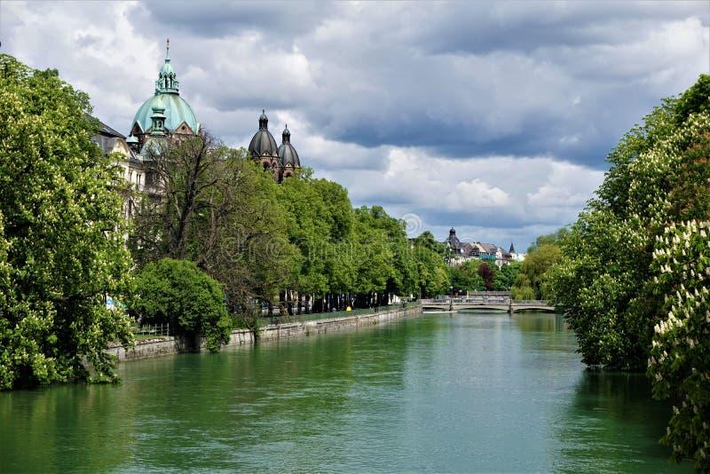 Den Isar floden i Munich med Sts Luke kyrkliga och kastanjebruna träd arkivfoto