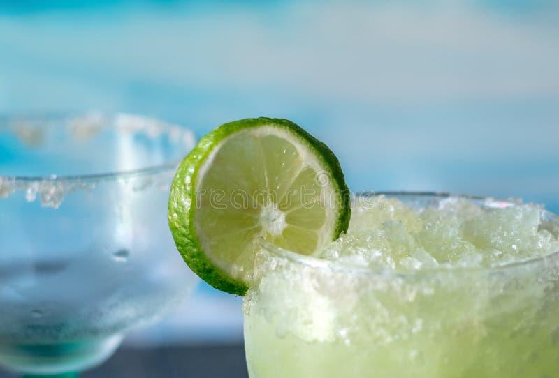 Den iskalla fryste margaritan dricker med skivor av limefrukt royaltyfria foton