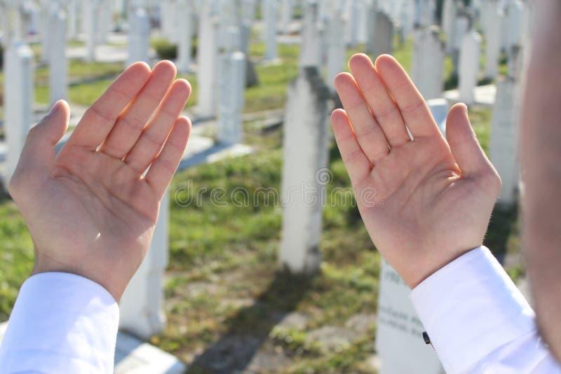 Den islamiska mannen ber på kyrkogården arkivfoton