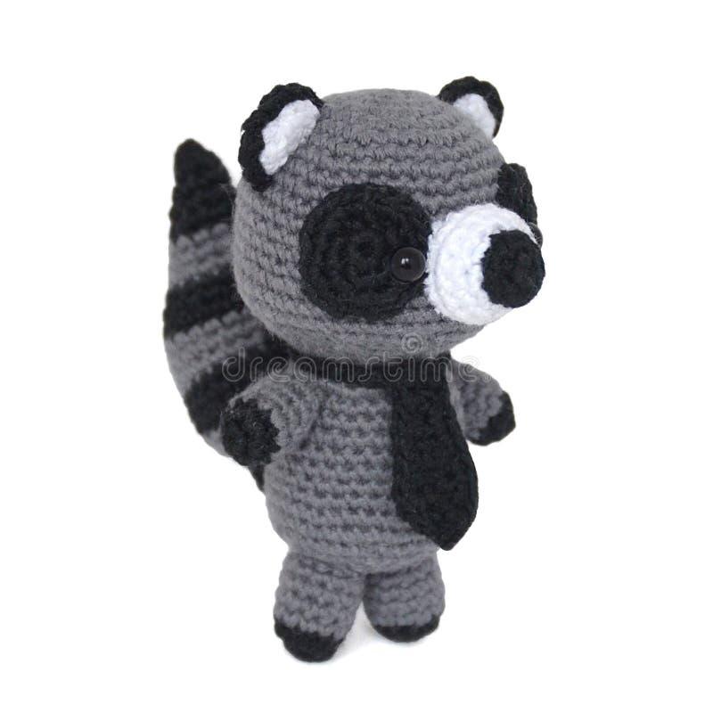 Den isolerade gråa tvättbjörnen för virkningleksaken i ett band står på dess bakre le arkivfoton